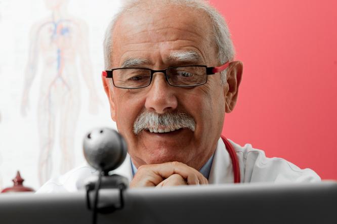 Senior doctor speaking with patient through webcam